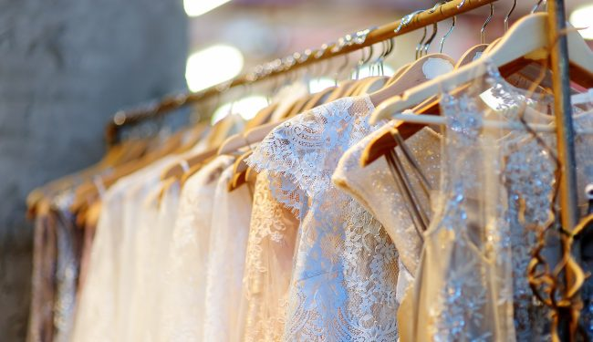 A few beautiful wedding dresses on a hanger.
