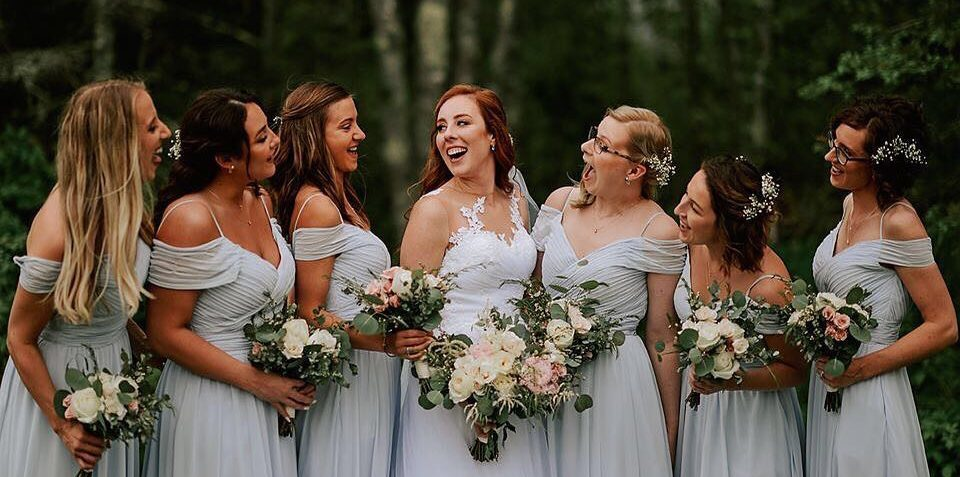 photo of bride and bridesmaids laughing in a forest