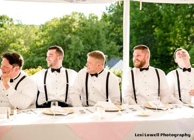 photo of five groomsmen laughing at a dining table